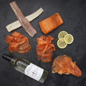 slices of smoked salmon with a bottle of white wine